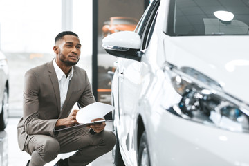 Insurance Agent Checking Car Taking Notes In Dealership Store