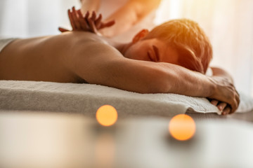 Sports massage. Massage therapist massaging shoulders of a male athlete, working with Trapezius muscle. Toned image. Masseur doing massage on man body in the spa salon. Beauty treatment concept.