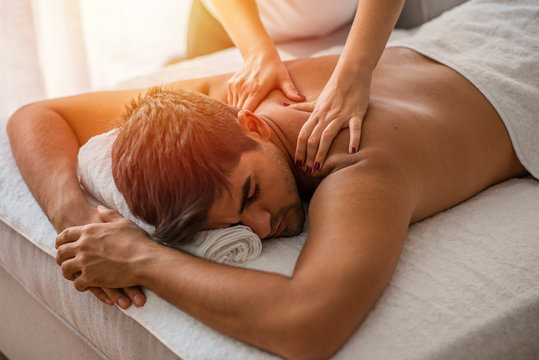 Man receiving back massage from masseur. Man having back massage at the health spa. Young Man Enjoying Massage At Spa. Relaxed mid adult man enjoying a back massage.