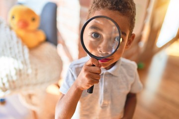 Beautiful african american toddler playing with loupe at kindergarten