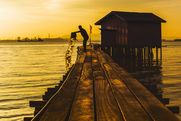 Silhouette of fisherman using net rowing catching fish in chew jetty village.