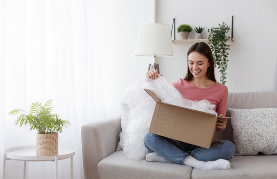 Excited young woman unwrapping parcel, buying goods via internet