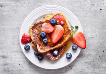 Delicious french toast with fresh fruits and maple sirup. Tasty breakfast scene or dessert with toast, strawberries, blueberries and powdered sugar. Fotobehang