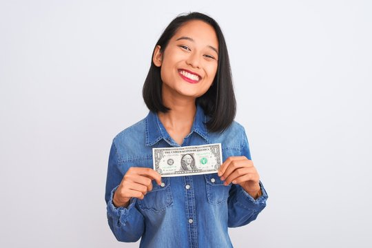 Young beautiful chinese woman holding one dollar standing over isolated white background with a happy face standing and smiling with a confident smile showing teeth