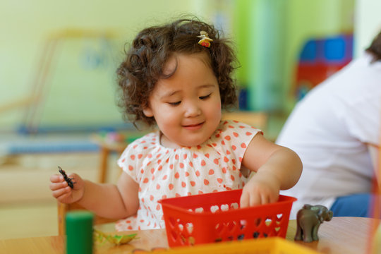 Pretty little kazakh girl sitting by the table and studying school lessons. Developing knowledge. Montessori education