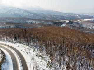 view of a road cutting through the mountain between Oatru and Niseko in Hokkaido, Japan