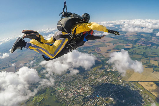 Skydive tandem free falling above the clouds
