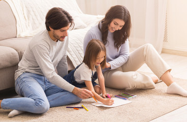Millennial Parents Drawing With Their Little Daughter On Floor At Home