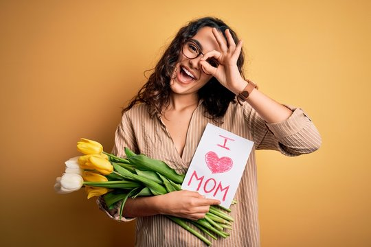 Beautiful curly hair woman holding love mom message and tulips celebrating mothers day with happy face smiling doing ok sign with hand on eye looking through fingers