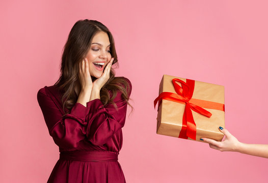 Excited young woman in evening dress getting surprise gift box