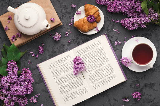 Spring flat lay with lilac, top view on flowers and book