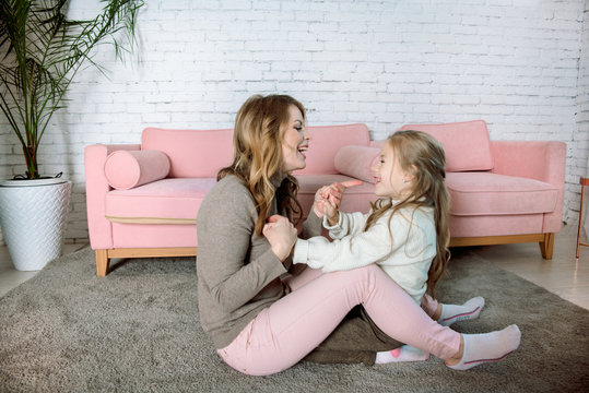 woman mother with child.Caring mother kisses and hugs the baby on the floor near the pink sofa. In a cozy house. Maternal love, parenting