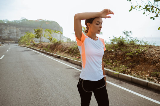 Fitness sport girl resting after intensive run walking on empty road