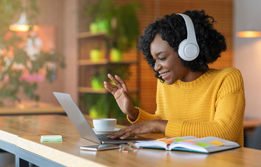Afro girl in headset using laptop, having skype conference