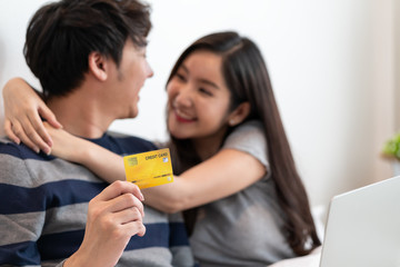 Portrait of a asian cheerful couple shopping online on internet with laptop computer while sitting at on the bed at home, man holding credit card with feeling happy for payment a gift to his wife