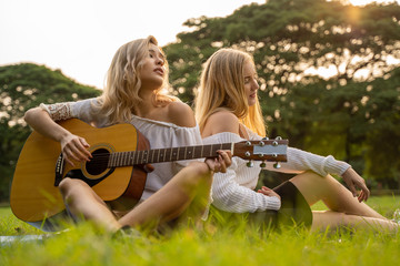 two young beautiful women friends outdoors playing a guitar and singing in park with sunset.