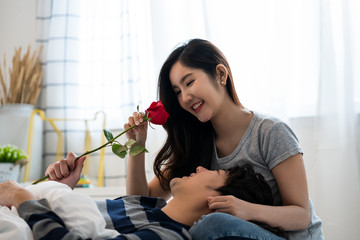 Romantic Asian couple in bedroom, a man giving a rose to beautiful woman and both kissing a beautiful rose with love and happiness, Beautiful elegant asian couple is hugging and smiling in bedroom.