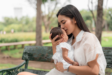 Asian young beautiful mother holding her newborn is sleeping and feel with love and touching gently then sitting on green grass in the park