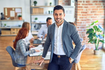 Group of business workers working together. Young handsome businessman standing smiling happy looking at the camera at the office Fotobehang