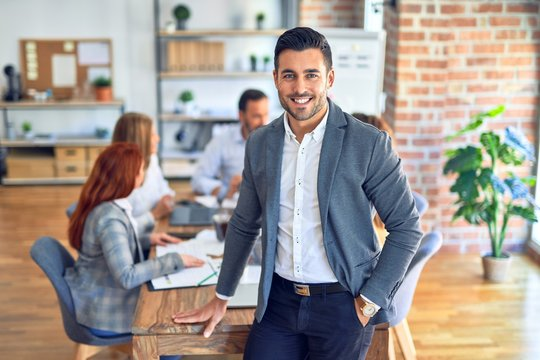 Group of business workers working together. Young handsome businessman standing smiling happy looking at the camera at the office