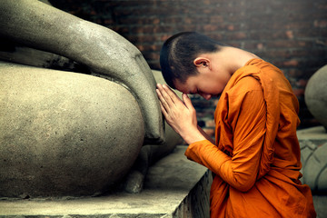 Asia novice monk worship the Buddha with faith.Buddhist monk sacred Buddha statue depicting a religious faith in a temple in country Southeast Asia. Fotomurales