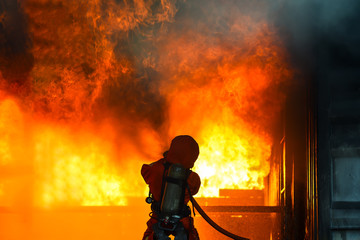 Foto op Textielframe Grandfailure Firefighters water spray with high pressure to fire surround with damaged house, godown. Firefighter fight with the fire.