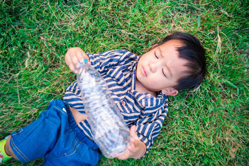 Adorable baby boy lying on green meadow grass with drink bottle