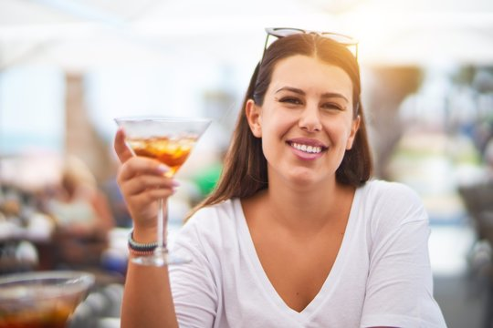 Young beautiful woman sitting at terrace of a restaurant drinking cocktail smiling