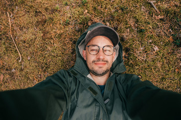Portrait of beautiful man lies on the ground in the forest against the background of spruce needles