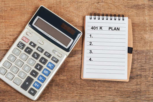 401 K plan list with calculator on wood table.