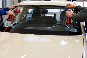 A professional mechanic changes a windshield on a car in a car workshop. Hands mechanic holding a tool. Replacement of automobile glasses.