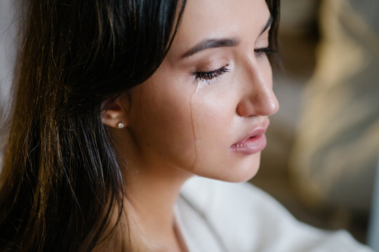 The girl is crying. Sadness is trouble chagrin depression tragedy loss  concept. Misfortune abuse divorce break off relations. Flowing tear. Emotional portrait of a beautiful caucasian women