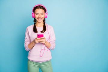 Photo of amazing pretty lady holding telephone cool bright earphones on ears listening youth radio wear casual stylish pink sweater trousers isolated blue color background