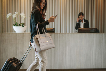 Fototapeta Business traveler in hotel hallway with phone obraz