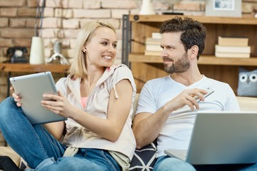 Young couple with laptop mobile and tablet