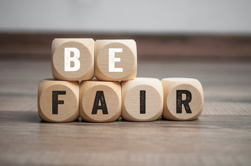 Cubes and dice with message Be fair on wooden background