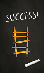 Black chalkboard with a ladder made of pencils and the word Success