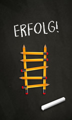 Black chalkboard with a ladder made of pencils and the german word for Success - Erfolg