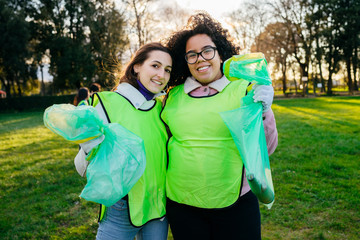 Two women friends show bags of rubbish collected during a event to clean park - Millennial having fun together