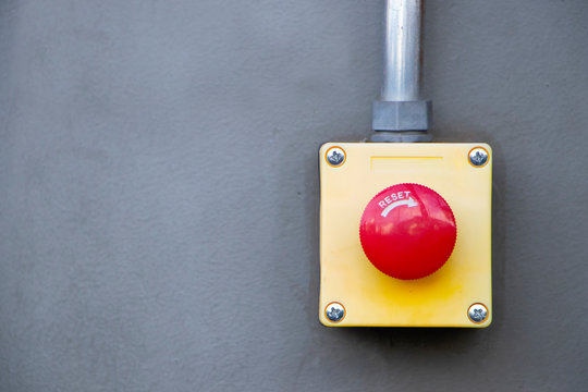 Red Reset button on the wall. red emergency stop switch button in a factory building.