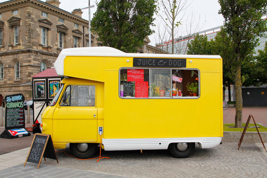 BELFAST, IRELAND - AUGUST 08, 2015: Yellow food truck of natural fruit juice and veggie food parked in the street, waiting for costumers at  the city of Belfast in Northern Ireland