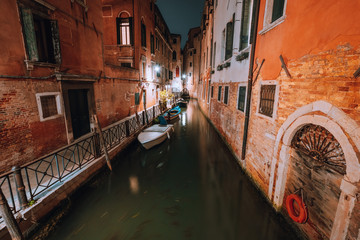 Venezia at night. Narrow channel and gondola boats in lagoon river city of venice. Long exposure photo