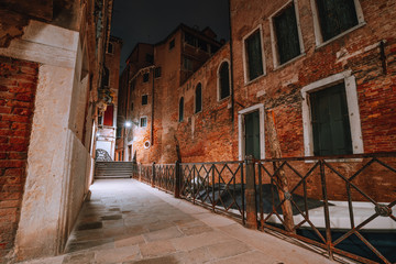 Gothic narrow streets with old red brick wall houses at night. Empty alleyways and bridge stairs in Venice, Italy