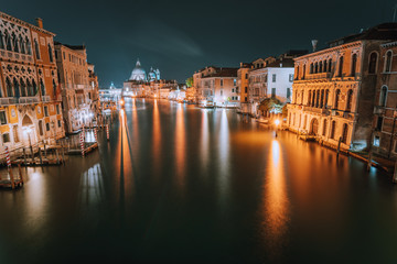 Venice, Italy. Night scene at Grand Canal with reflected light at water surface. Majestic Basilica di Santa Maria della Salute in background