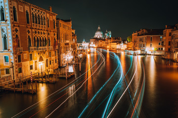 Venice twilight blue night scenery. Light illuminated trails of ferries and boats reflected on the Grand Canal surface. Majestic Basilica di Santa Maria della Salute in background. Italy
