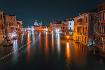 Venice, Italy night scenery of Grand Canal. Vivid light trails of ferries and boats reflected on water surface. Majestic Basilica di Santa Maria della Salute in background