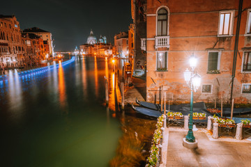 Venice, Italy night scenery of Grand Canal lit by lanterns and reflected on water surface. Majestic Basilica di Santa Maria della Salute in background