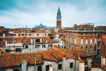 Venice, Italy. Rooftop view, roofs of traditional old houses in Venice. Venezia, overlooking houses roofs and beautiful blue sky