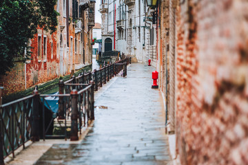Venice, Italy. The small streets and narrow channel with colored brick houses on the shore of old city