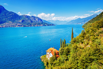 Wall Mural - Lake Como in Italy, summer time view over red roof of lonely house villa at azure background of blue water surface, blue sky and mountains. Como lake is popular luxury travel destination in Italy.